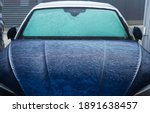 Modern Blue Body Car Covered in Frost During Freezing Cold Winter Morning. Front of the Vehicle. Seasonal Automotive Maintenance and Weather Elements. - stock photo
