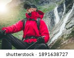 Outdoor Recreation. Active Caucasian Hiker Wearing Red Rainproof Jacket and Eyes Safety Glasses Seating Next to Scenic Alpine Waterfalls. Exploring the Trail. - stock photo
