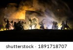 Small photo of Medieval battle scene. Silhouettes of figures as separate objects, fight between warriors at night. Creative artwork decoration. Foggy background. Selective focus