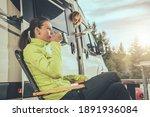 Caucasian Friends RV Weekend Getaway. Woman Drinking Hot Tea From Metal Cup. Her Friend Leaving Camper Van.  - stock photo