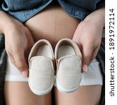 Pregnant Mother Hold Baby Shoes