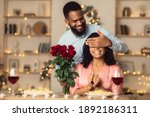 Small photo of Greeting With Holidays. Smiling black man covering his woman eyes and giving her bunch of red roses, making surprise to beautiful lady. African american couple celebrating together at home or cafe