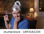 Small photo of Nervous man wearing tin foil hat holding syringe
