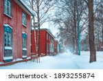 Small photo of Snowstorm in Helsinki. Beautiful Finnish winter scene. Colorful building facades at a street covered in snow. Old red wooden houses in town in Finland. Traditional Finnish architecture. Cold weather.