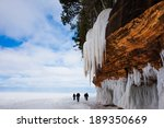 Frozen Lake Superior shoreline.  Orange cliff, large icicles, people for scale.  Copy space.  Apostle Islands National Lakeshore on Lake Superior.  Popular winter travel destination.