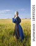Small photo of An Amish woman standing in a grassy field in afternoon sunlight