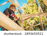 Caucasian Construction Worker in His 40s Between Wooden Roof Elements of the House Skeleton Frame. Construction Industry Theme. - stock photo