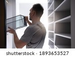 Caucasian Men in His 40s Finishing His Brand New Apartment Closet Inserting Last Metal Drawer Bucket Into Furniture Element. - stock photo