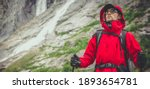 Outdoor Sport and Recreation Theme. Caucasian Hiker in His 30s Wearing Red Raincoat and Safety Sport Glasses on the Scenic Alpine Trailhead. Rocks and Waterfalls in a Background. - stock photo