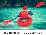 Caucasian Kayaker on the Scenic Glacial Lake Trip. Turquoise Water Color and Red Kayak. Kayaker Rear View. Recreation and Summer Water Sports Theme. - stock photo