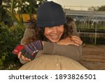 Small photo of Relent the real skin of the farmer Thai, Asian women aged 50 years hold the smartphone in hand and smile authentic. Dressed like a soldier, laying relax, smiling happily on a log, blurred background .