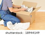 woman unpacking moving box in... | Shutterstock . vector #18944149