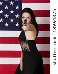 Beautiful young woman with long hair holding a .45 cal automatic pistol in front of an American flag. - stock photo