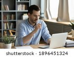 Small photo of Concentrated young businessman in eyewear looking at laptop screen, web surfing information in internet or working distantly online at home office, communication remotely with client or study.