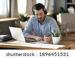 Small photo of Focused young businessman in eyeglasses wearing wireless headset with microphone, involved in online video call negotiations meeting with partners colleagues or studying distantly, writing notes.