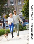 Stock photo couple taking dog for walk in city park 189676397