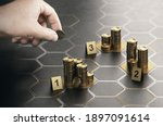 Small photo of Human hand stacking coins over black background with hexagonal golden shapes. Concept of angel investor and investing in startup companies. Composite image between a hand photography and a 3D backgrou