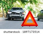 Small photo of Red emergency stop triangle sign on road during a car accident. Broken gray car in road traffic accident. Car crash traffic accident on city road after collision