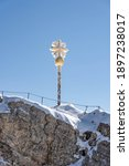 Gold cross at top of Zugspitze coverd in snow in summer morning