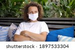 Small photo of Young white woman in protective face mask sitting alone outdoors staring far away thinking about something. Palmy leaves on a background