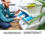 Small photo of A young adult man throwing a piece of paper into a recycling bin, container for paper. Waste segregation at home.