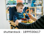 Small photo of Activities for kids with disabilities. Preschool Activities for Children with Special Needs. Boy with with Cerebral Palsy in special chair play with mom at home.