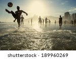 Stock photo carioca brazilians playing altinho beach football in silhouettes kicking soccer balls in the waves 189960269