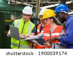 Small photo of Diversity factory worker working with computer laptop in factory. Male and female worker wearing safety uniform, helmet and gloves at work factory. Group of worker working at factory
