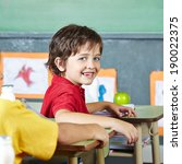 Small photo of Happy abecedarian child sitting smiling in elementary school classroom