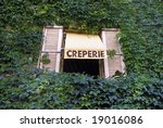 Sign for a French Creperie above a window in a wall grown with ivory - stock photo