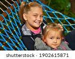 Children Sit In A Hammock....