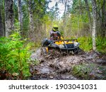 Small photo of ATV racer in mud. He drives off-road in forest. ATV racer in taiga. Motocross in summer taiga. Extreme quad cycle riding. Ride through green forest on quad cycle. Motocross on a quad cycle