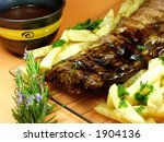 Barbequed baby back ribs with french fries on a plate. - stock photo