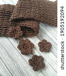 Small photo of crochet warm scarf and crochet flower on wooden table. crochet with cotton yarn.