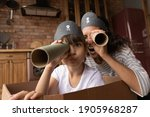 Small photo of Head shot portrait happy mother and little daughter playing pirates, looking at camera, excited mum and preschool gild child wearing handmade costumes, holding paper tubes as spyglass, having fun