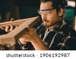 Small photo of Carpenter man professional skilled in wood work looking detail of masterpiece woodcraft in furniture workshop