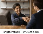 Small photo of Greetings, you are hired. Happy young indian female successful job seeker shake hand of male hr manager being accepted on vacant place. Diverse business partners handshake close deal come to agreement