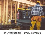 Small photo of Caucasian Construction Contractor in His 40s and His Modern Black Pickup Truck. Men Preparing His Tools For the Job. Wooden House Skeleton in Background.