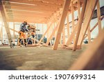 Small photo of Caucasian Contractor Carpenter Worker in His 40s Using Commercial Grade Circular Saw in Construction Zone. Industrial Theme. Wooden Skeleton Framing Building.