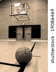 Basketball on court with hoop in the background - stock photo