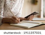 Small photo of Crop close up of woman make notes handwrite in notebook using modern cellphone gadget. Female student study distant with smartphone summarize write or list in notepad. Technology concept.