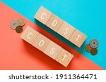 """Small photo of COST vs COST; Eight wooden blocks with """"COST"""" text of concept and many coins."""