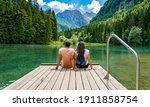 Rear view of young female sitting on wooden deck by beautiful lake in mountains  Green, spring, flower crown, outdoors  Zgornje Jezersko, Slovenia