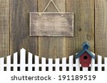 Blank wood sign over white picket fence with birdhouse
