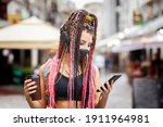 Small photo of Playful cool rebel funky hipster young girl with face mask searching for playlist music on mobile phone app while walking on city street – Street fashion and new normal concept of youth generation