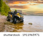 Quad bike on the river bank. The ATV driver drove into water. Quad bike on the background sunset. A man travels on a quad bike. A yellow ATV stands in lake. Concept - outdoor activity.