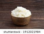 Small photo of Freshly Churned White Butter Also Known As Safed Makhan Malai Or Homemade Makkhan In India Is Used To Prepare Desi Ghee In Brass Bowl. Isolated On Brown Wooden Background With Copy Space For Text