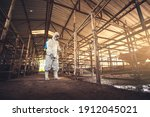 Small photo of People wearing personal protective equipment or PPE with spraying disinfectant for protection pandemic of disease in cattle farm. Agriculture cattle farm industry.