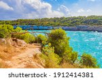 Small photo of Turquoise water and nature walking path at bay Calo d'en Garrot Mallorca Balearic Islands Spain.