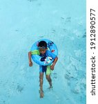 Small photo of Terengganu, Malaysia : 8 December 2019, A cute young boy swimming in a pool with floater. Selective focus on face and image contains noise and grain effect.